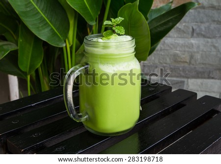 Green tea smoothies in glass on black wooden table. selective focus