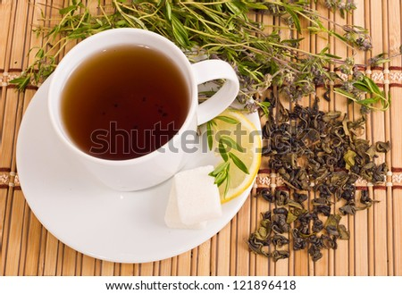 green tea with herbs and lemon on bamboo mat background