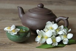 Green tea with Jasmine flowers and Chinese ceramic teapot.