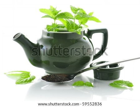 green teapot with mint plant and loose tea
