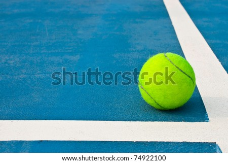 Green tennis ball on blue court
