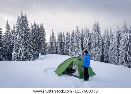 Green tent and tourist against the backdrop of snowy pine tree forest. Amazing winter landscape. Tourists camp in high mountains. Travel concept #1157600938
