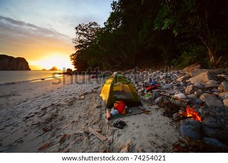 Green tent on sandy wild beach at sunset light