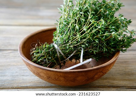 Green thyme in a bowl on boards, close up