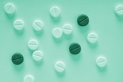 Green tinted background on the theme of medicine, health care, drugs, pharmacology. Light tablets and dark pills lie on paper sheet. Pharmacological backdrop close-up. Top view from above. Macro