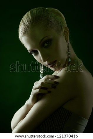 green tinted portrait of beautiful young blonde woman in jewelry with manicured fingers
