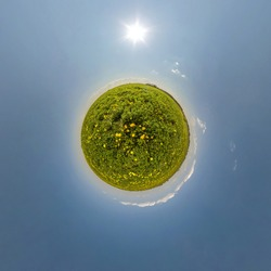 green tiny planet in blue sky with beautiful clouds. Transformation of spherical panorama 360 degrees. Spherical abstract aerial view. Curvature of space.