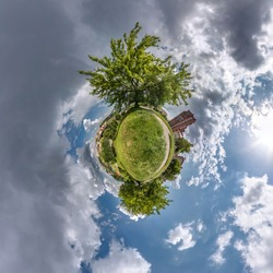 green tiny planet in blue sky with sun and beautiful clouds. Transformation of spherical panorama 360 degrees. Spherical abstract aerial view. Curvature of space.