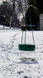Green tire swing in neighborhood yard in snow with shadows and footprints leading from neighbors yard to swing.