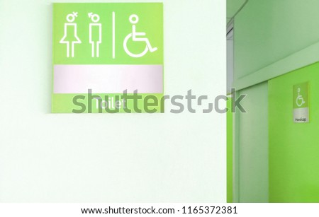 Green toilet sign in front of toilet room or rest room with man, woman and handicap icon set  symbol on white concrete wall background, modern, hygiene and clean restroom concept #1165372381