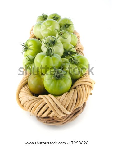 Green tomatoes in a basket isolated on white background. - stock photo