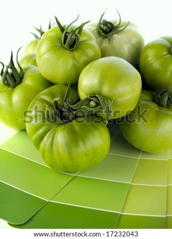 Green tomatoes with matching green paint color swatches.