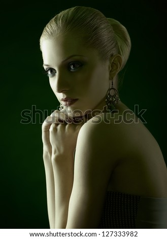 green toned portrait of beautiful young blonde woman in jewelry