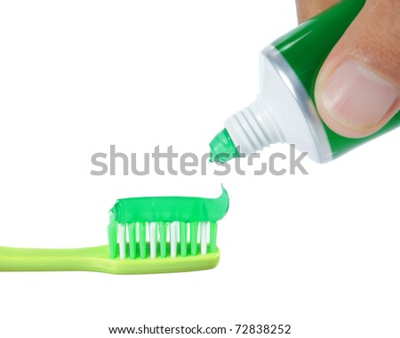 green tooth brush with green mint tooth paste on top of it