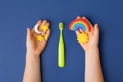 Green Toothbrush and kid hands with decorative Sun, rainbow, moon and stars on classic blue background. Care about teeth in morning and evening. Daily routine concept. Health care concept