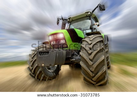Green tractor in motion with a cloudy sky