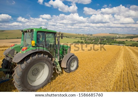 Green tractor in sunny rural field