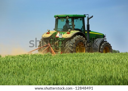 Green tractor working in the field.