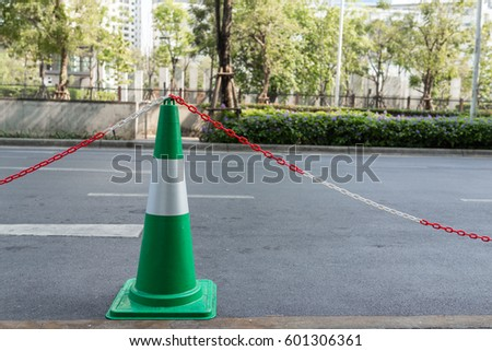 green traffic cone with red and white chains for taxi parking #601306361