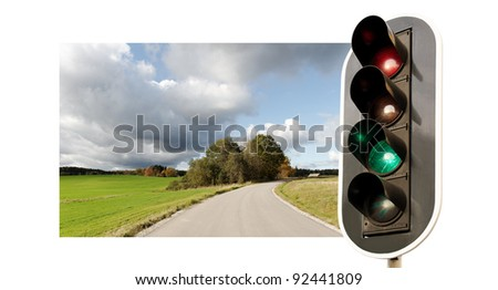 Green traffic light on white isolated background and country landscape.