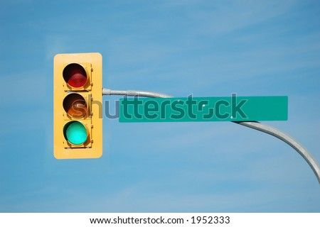 Green traffic light with blank sign.