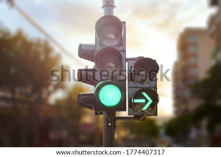 Green traffic light with green arrow light up in city while sunset allows car to turn right