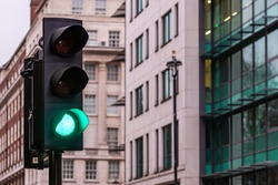 Green traffic lights for cars on a blurred buildings background - image