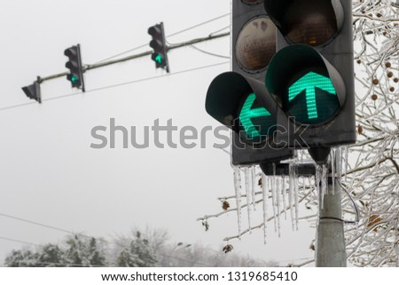 Green traffic lights for forward and left turns, with icicles haging from them, during Winter season, after days of rain turned to ice. #1319685410