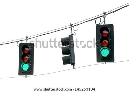 Green traffic lights swinging from wires overhead.  Close up on white background.