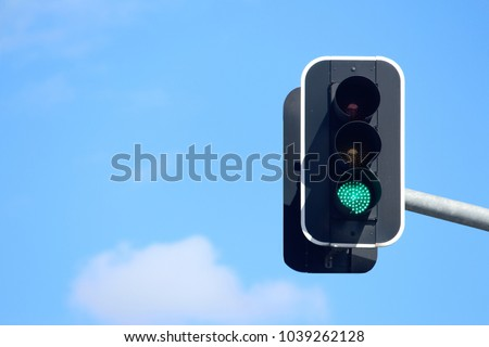 Green traffic lights with a sky background
