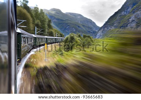 Green train moving in the mountains. Norway.