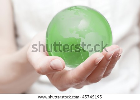 Green transparent earth globe in the hand with shallow DOF.Earth saving concept.