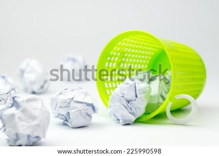 Green trash bin and crumpled paper balls on white background