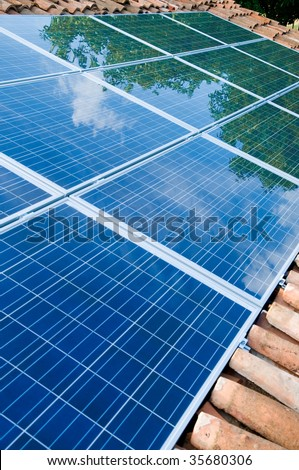 Green trees and blue sky reflection on solar panels mounted on a roof. Go green with renewable energy!