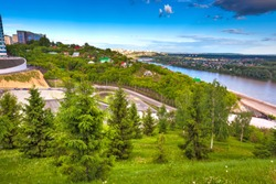 Green trees on the slope in front of the panorama of the city and the river flowing below on a bright sunny day. Multicolored private houses. Park of Salavat Yulayev, Ufa, Bashkortostan, Russia.
