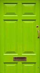 green typical residential house door in Ireland (golden lock, handle and mailbox)