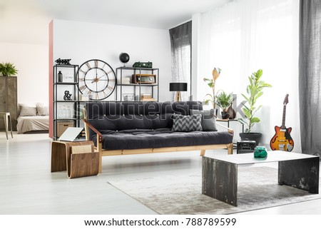 Green vase in front of a dark sofa and wooden table with laptop in man's apartment interior with guitar