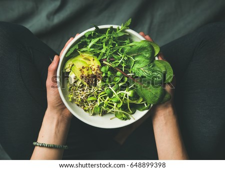 Photo of  Green vegan breakfast meal in bowl with spinach, arugula, avocado, seeds and sprouts. Girl in leggins holding plate with hands visible, top view. Clean eating, dieting, vegan food concept