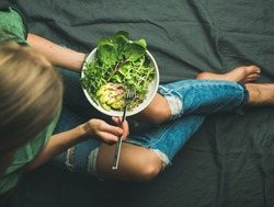 Green vegan breakfast meal in bowl with spinach, arugula, avocado, seeds and sprouts. Girl in jeans holding fork with knees and hands visible, top view. Clean eating, detox, vegetarian food concept
