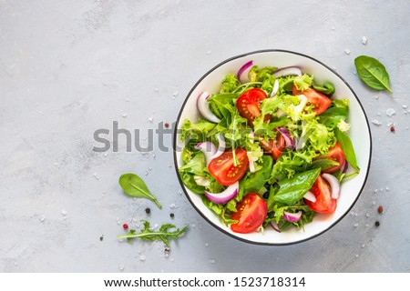 Green vegan salad from green leaves mix and vegetables. Top view on gray stone table. Foto d'archivio ©