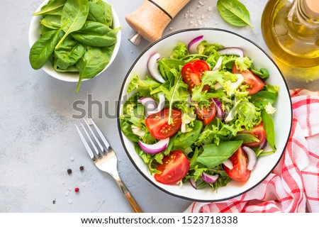 Green vegan salad from green leaves mix and vegetables. Top view on gray stone table. Stock photo ©