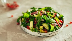 Green vegetable salad with ruccola, pomegranate seeds, avocado, onions and herbs. Gray concrete background. Thyme. Horizontal orientation
