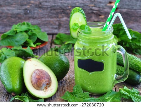 Green vegetable smoothie on wood background