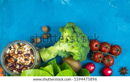 Green vegetables on a blue background.  Vegetarian vegetarian dietary background: zucchini, peppers, broccoli, tomatoes, salad, beans, carrots, greens, flakes with dried fruits.  Healthy lifestyle