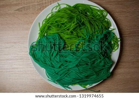 green vegetarian vermicelli. green vegetarian pasta. Vegetarian healthy food on white plate. green vegetarian pasta closeup photo #1319974655