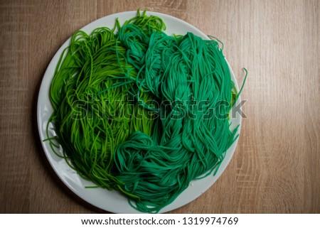 green vegetarian vermicelli. green vegetarian pasta. Vegetarian healthy food on white plate. green vegetarian pasta closeup photo