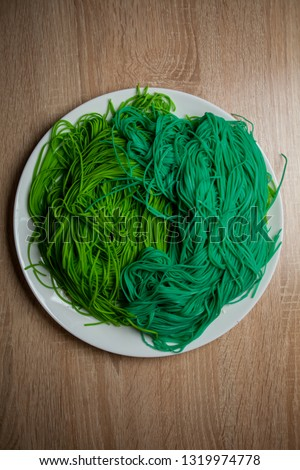 green vegetarian vermicelli. green vegetarian pasta. Vegetarian healthy food on white plate. green vegetarian pasta closeup photo #1319974778
