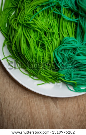 green vegetarian vermicelli. green vegetarian pasta. Vegetarian healthy food on white plate. green vegetarian pasta closeup photo #1319975282