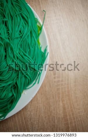 green vegetarian vermicelli. green vegetarian pasta. Vegetarian healthy food on white plate. green vegetarian pasta closeup photo #1319976893