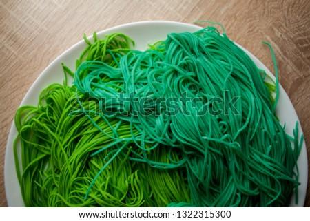 green vegetarian vermicelli. green vegetarian pasta. Vegetarian healthy food on white plate. green vegetarian pasta closeup photo #1322315300